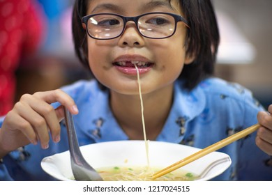 Portrait Asian girl wating the egg noodle with soup. Cute little girl eating the noodle with funny face