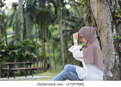 portrait of  Asian girl wearing hijab with multiple expression at the park by evening.