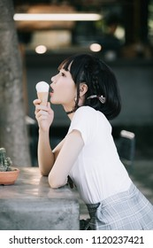portrait of asian girl with white shirt and skirt eating ice cream in outdoor nature vintage film style