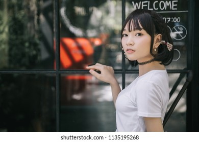 portrait of asian girl with white shirt and skirt looking in outdoor nature vintage film style