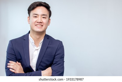 Portrait of Asian handsome business man wearing formal suit, cross his arms and smiling with confident with white background