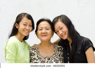portrait of asian happy family embracing each other, grandmother and two granddaughter