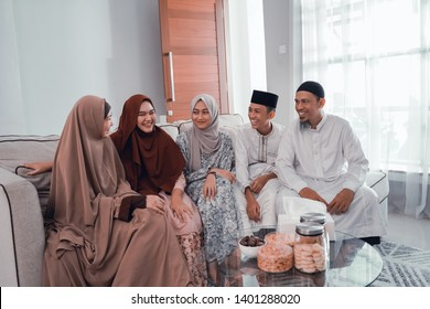 portrait of asian happy muslim family sitting on the couch at home