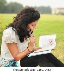 Portrait of an Asian / Indian college student thinking while reading a book at campus.