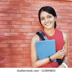 Portrait of an Asian / Indian college student on the red brick wall.