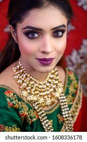 Portrait of Asian/ Indian female model in Bridal makeup with heavy jewelry. Bengali, Marwari , Punjabi and south Indian bride makeup.