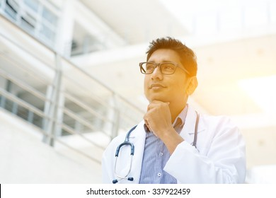Portrait of Asian Indian medical doctor thinking and looking away, standing outside hospital building, beautiful golden sunlight at background.