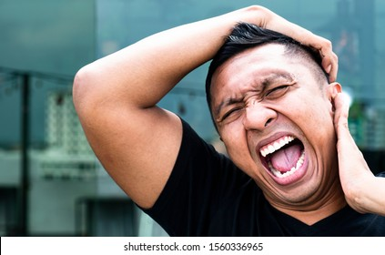 A portrait of an Asian Indonesian male model who loses his mind and cool. Frustrated and going crazy,  he puts arms behind his head and starts screaming with his mouth open wide showing his teeth