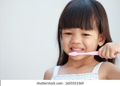 Portrait Asian kid girls aged 4 to 6 years, long hair wearing a white shirt Pretty face Happily brushing his teeth The hand holds a pink toothbrush.Brushing teeth makes her teeth strong.