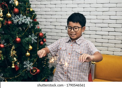 Portrait of Asian kid holding sparklers in his two hands; Christmas and New Year celebration concept