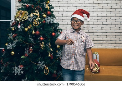 Portrait of Asian kid with red hat holding sparklers in his two hands; Christmas and New Year celebration concept