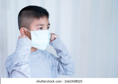 Portrait Asian kid wearing medical mask.A boy wearing mouth mask against air smog pollution. Concept of corona virus quarantine or covid-19.Protection against virus and infection control concept.