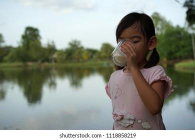 Portrait Asian kids little girl Drinking milk from glass