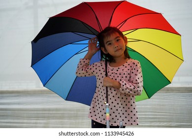 Portrait Asian kids little girl hold Multi colored rainbow umbrella