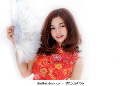 Portrait of Asian lady holding Chinese fan in hand with cheongsam dress or Qipao on white background. Chinese traditional costume to celebrate Chinese new year