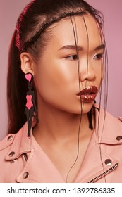 Portrait of Asian lady, wearing pink leather jacket, posing on pink background, looking to side. The girl with wet hair locks on her face is wearing long dangle earrings in the view of a cat woman.