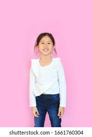 Portrait asian little child girl smiling and looking camera over pink background.