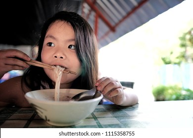 Portrait of Asian little cute girl eating delicious thai noodles with chopstick by herself.Food,Family,Childhood Concept.