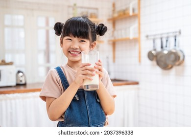 Portrait of Asian little cute kid holding a cup of milk in kitchen in house. Young preschool child girl or daughter stay home with smiling face, feel happy enjoy drinking milk and then look at camera. - Shutterstock ID 2037396338