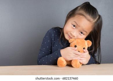 Portrait of asian little girl play and hug teddy bear with love
