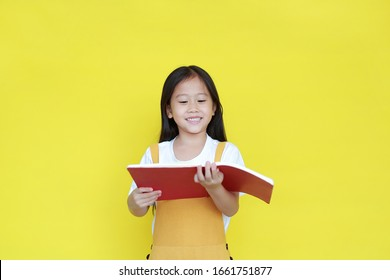 Portrait asian little girl reading book isolated on yellow background. Schoolgirl smiling while study. Back to School and education concept