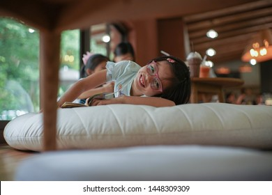 Portrait Asian little girl smiles with dimples on her cheek and looks at the camera with blurred bokeh light in coffee shop and cafe. Declining girl with eyeglasses lying down on the pillow