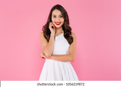 Portrait of asian lovely woman with dark curly hair in white dress posing with kind smile isolated over pink background