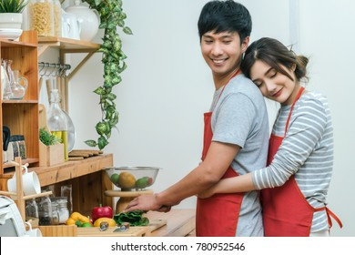 Portrait of Asian Lover or Couple hugging and cooking with smiling action in the kitchen room at the modern house, Couple and life style concept.
