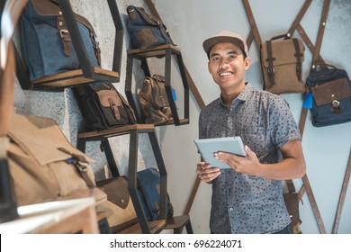 portrait of asian male business owner standing in front of his bag store with tablet