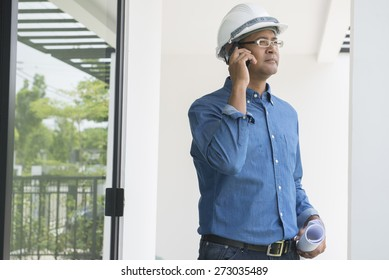 Portrait of  Asian male contractor engineer with hard hat using mobile phone