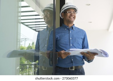 Portrait of  Asian male contractor engineer with hard hat holding paper work