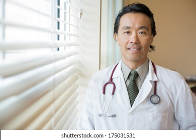 Portrait of Asian male doctor with stethoscope around neck standing in hospital room