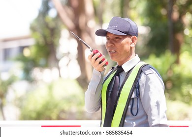 Portrait Of Asian Male Security Guard Talking a portable wireless transceiver entrance the village on a blurry background,use a filter