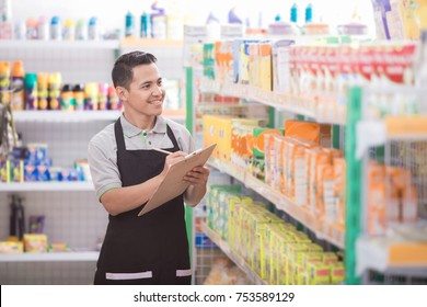 Portrait of asian male staff checking the product in supermarket