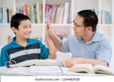 Portrait of an Asian male teacher doing high five with his student while studying together in the library