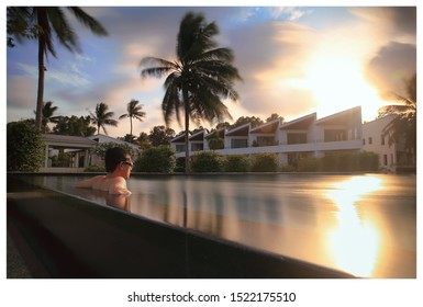 Portrait of a Asian man enjoying swimming in the poolon his holiday  during sunset time.