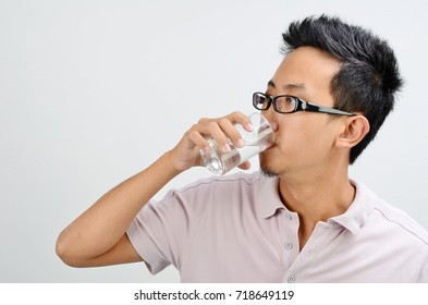 Portrait of Asian man hand holding glass drinking mineral water, standing isolated on plain background.