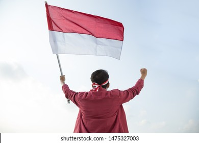 Portrait of asian man holding a Indonesian red and white  flag under a bright blue sky