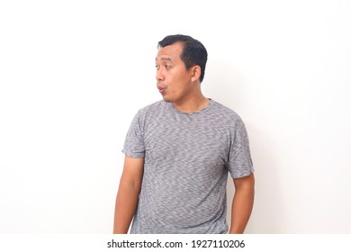 Portrait of Asian man looking sideways while whistling. Isolated on white background with copyspace