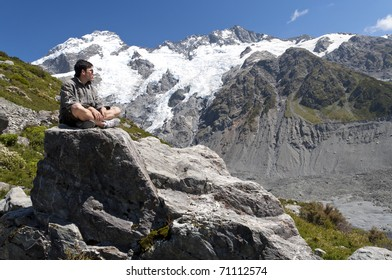 Portrait of Asian man sitting over Tasman Glacier, New Zealand