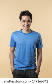 Portrait of Asian man standing against cream background.