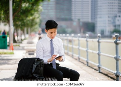 1b233311edbc Portrait of Asian man typing in his smartphone. He s seated on a bench  along the