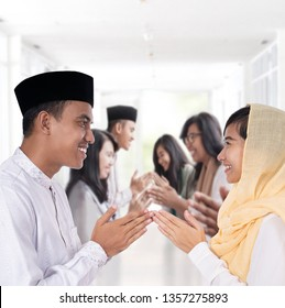 portrait of asian man and woman greeting in muslim traditional way touching tip of finger