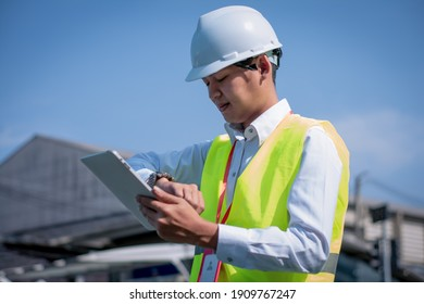 Portrait asian manager engineer in hardhat at work on outside industrial,using digital tablet control work and survey building construction factory site,concept action business working and industry.