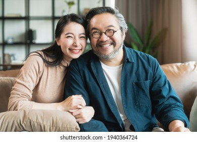 Portrait of Asian mature couple sitting and smiling in living room. wife woman hand hold husband arm from behind and look at camera with happiness and cheerful safty amd insurance family concept