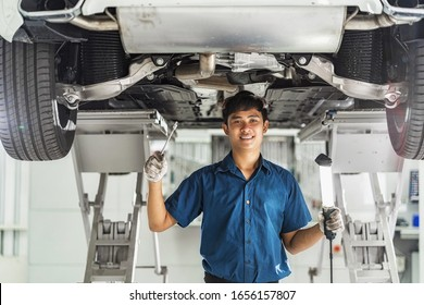 Portrait of Asian mechanic with repair equipment standing under the car in maintainance service center which is a part of showroom, technician or engineer professional work for customer