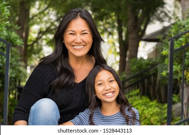 Portrait of an Asian mom and her daughter outside.