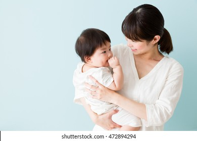 portrait of asian mother and baby isolated on blue background