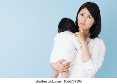 portrait of asian mother and baby on blue background
