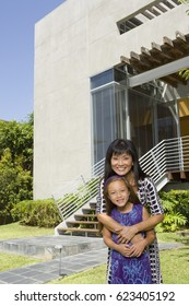 Portrait of Asian mother and daughter in front of house